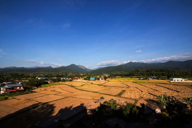 Uitzicht op bergen en rijstvelden na de oogst op blauwe hemel