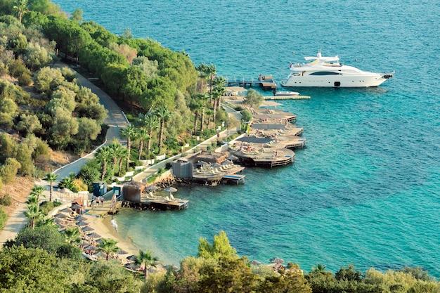 Uitzicht op blauwe egeïsche zee, wit jacht in kleine pier in de buurt van hotel.
