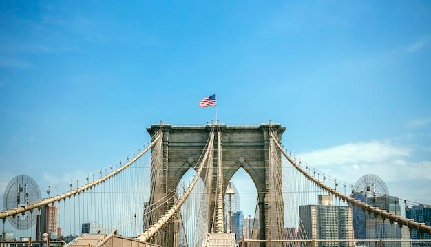 Uitzicht op brooklyn bridge torent hoog boven de blauwe lucht met de skyline van manhattan op de achtergrond, in new york city