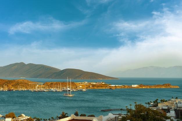 Uitzicht op de baai van bodrum, turkije met jacht en bergen op een mooie zonnige dag met bewolkte blauwe lucht