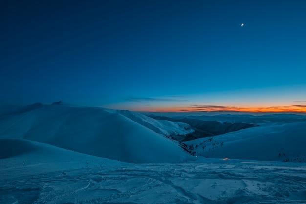 Uitzicht op de bergen en heuvels in de besneeuwde vallei in de late avond