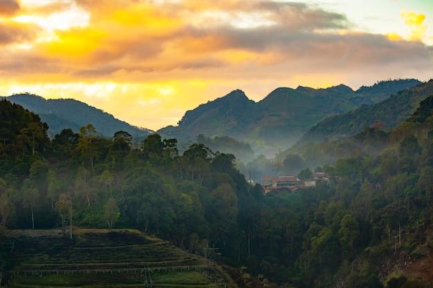 Uitzicht op de bergen, gele lucht en mist