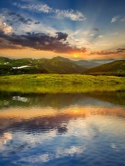 Uitzicht op de bergen met een meer bij zonsondergang