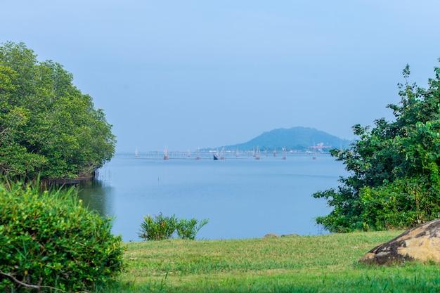 Uitzicht op de bergen vanaf songkhla meer, thailand met bomen en vissen kooien in het midden.