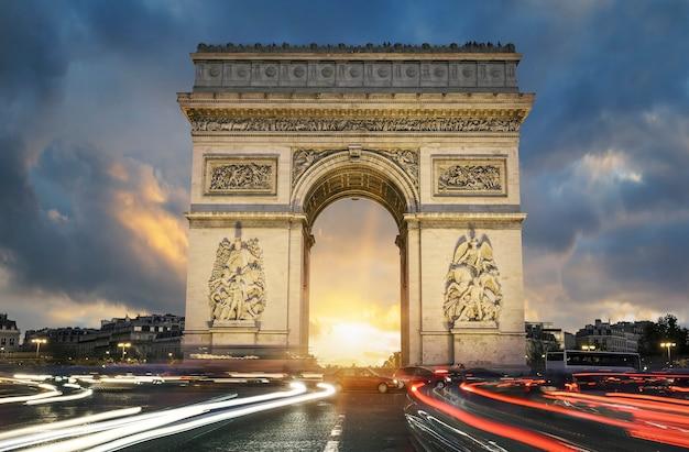 Uitzicht op de beroemde arc de triomphe bij zonsondergang, parijs