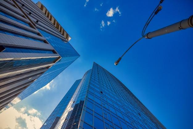Uitzicht op de commerciële glazen wolkenkrabber toren tegen de blauwe lucht - van onder naar boven geschoten