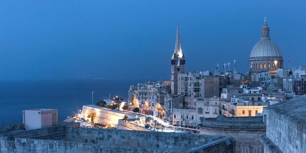 Uitzicht op de daken van de oude stad, het fort, de kerk van onze lieve vrouw van de berg karmel en de st. paul's anglicaanse pro-kathedraal 's nachts, valletta, hoofdstad van malta