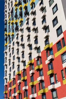 Uitzicht op de gevel van een woongebouw met meerdere verdiepingen. kleurrijke elementen in het ontwerp van het gebouw