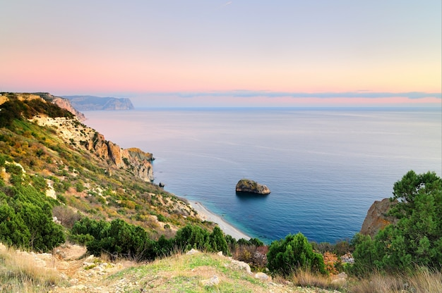 Uitzicht op de heuvels met de kalme zee en de roze zonsondergang