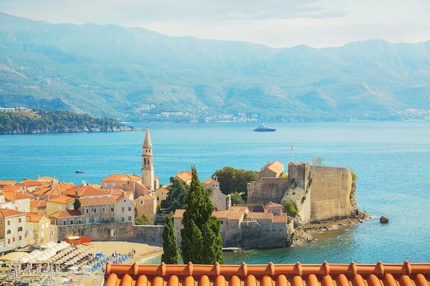 Uitzicht op de kerk van st ivan, oude muren, bergen en zee in de oude stad budva, montenegro