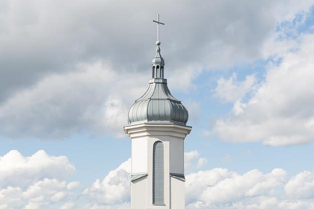 Uitzicht op de koepel en de klokkentoren van een moderne katholieke kerk tegen een blauwe hemel met wolken. conceptarchitectuur, pasen, religie.