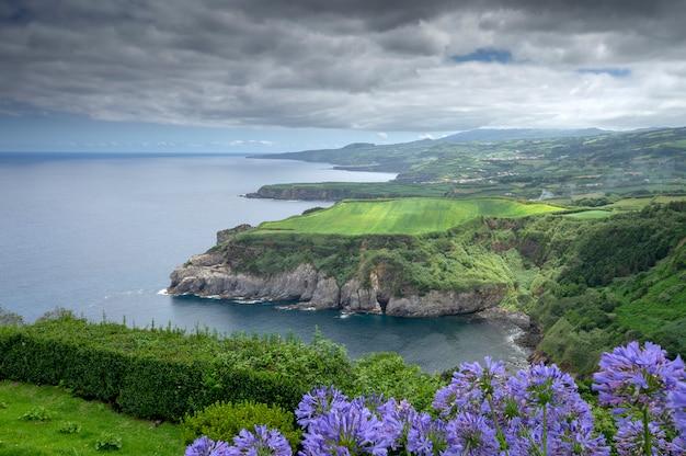 Uitzicht op de kust en de kliffen met overvloedige vegetatie in de dag met wolken. sao miguel. azoren eiland. portugal