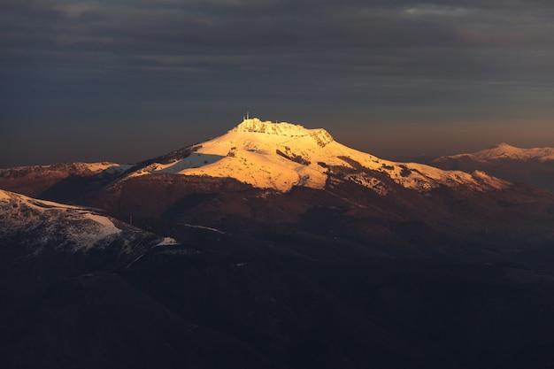 Uitzicht op de larrun berg vallende sneeuw op een winteravond baskenland.
