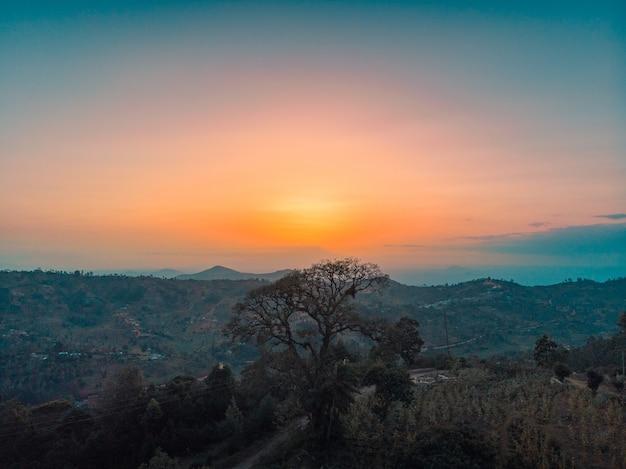 Uitzicht op de met bomen bedekte heuvels met de zonsondergang