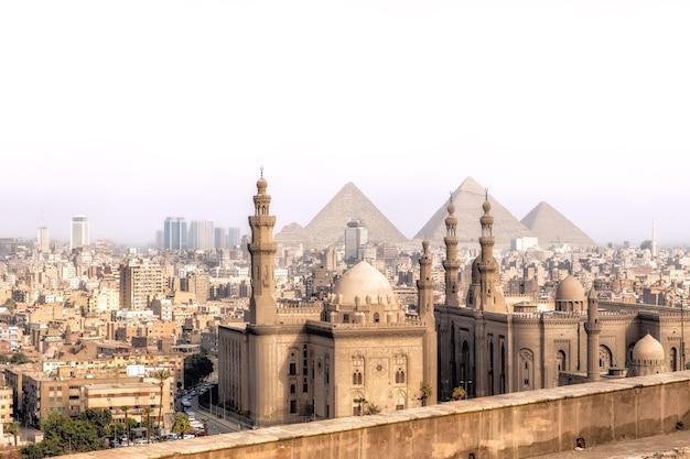 Uitzicht op de moskee-madrassa van sultan hassan in caïro en de piramides van gizeh, egypte.