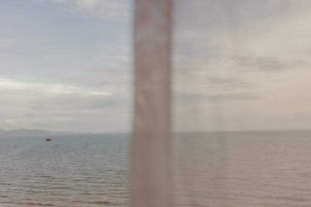 Uitzicht op de oceaan door dun wit gordijn in de zomer
