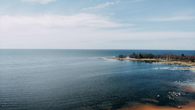 Uitzicht op de oceaan kust van quadcopter, zand en rotsen aan de zeekust. ocean shore bovenaanzicht. horizon en blauw water.