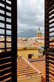 Uitzicht op de oude stad van palermo op sicilië door het open raam met luiken, italië