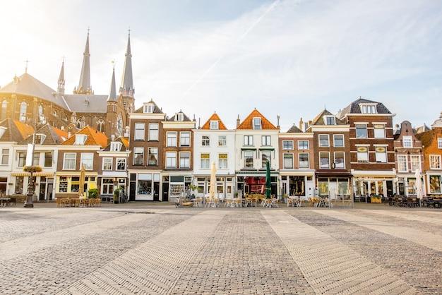 Uitzicht op de prachtige gevels van gebouwen en de kerk op het centrale plein tijdens de zonnige ochtend in de stad delft, nederland