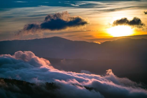 Uitzicht op de prachtige zonsondergang in bergdal. heuvels omgeven door wolken met dramatische hemel op achtergrond. concept van natuurschoonheid en zonsondergang.