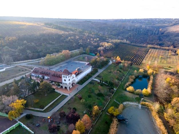 Uitzicht op de purcari winery vanaf de drone. hoofdgebouw met wandelpaden, groen en twee meren. dorp in de verte, moldavië
