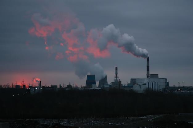 Uitzicht op de rokende schoorstenen van een thermische elektriciteitscentrale in de eerste zonnestralen