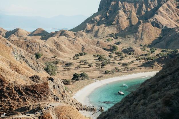 Uitzicht op de savanneheuvels op padar island met kust en boot