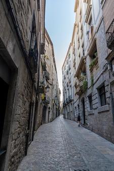 Uitzicht op de smalle straatjes van het oude centrum van girona met een vrouw.