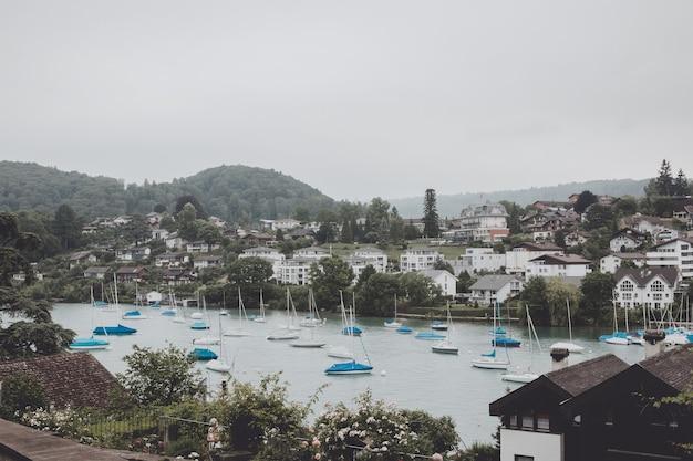 Uitzicht op de stad spiez en het meer van thun, zwitserland, europa. zomerzondag, dramatische blauwe bewolkte lucht en verre bergen