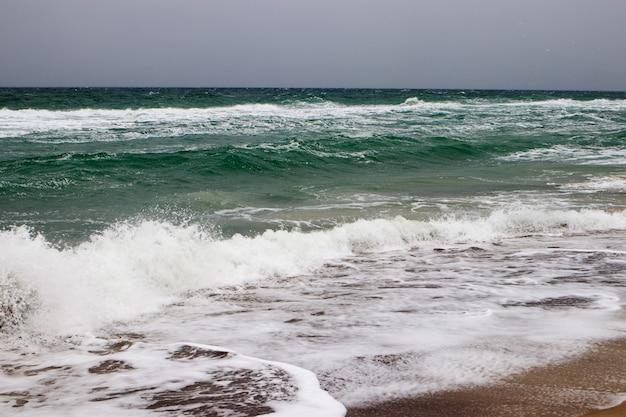 Uitzicht op de stormachtige zee vanaf de kust