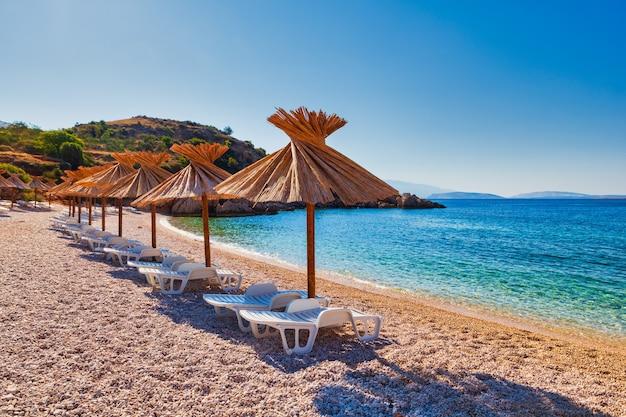 Uitzicht op de stro parasols op het prachtige strand van oprna in de adriatische baai van het eiland krk, in kroatië
