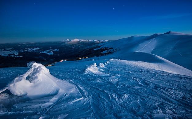 Uitzicht op de vallei van het skigebied met heuvels en bergen 's nachts