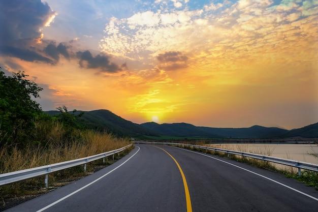 Uitzicht op de verharde weg in de ochtend met bergen en rivieren en deels bewolkt