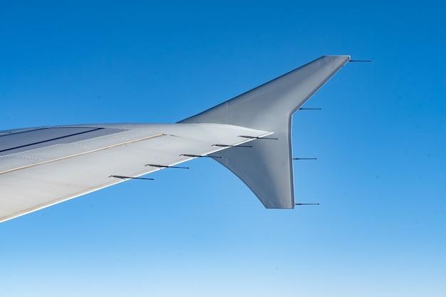 Uitzicht op de vleugel van het vliegtuig en de heldere blauwe lucht