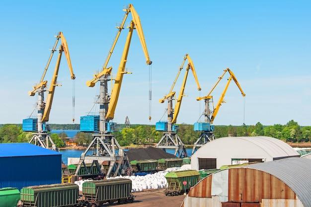 Uitzicht op de vrachthaven, met hoge zeekranen voor het laden van goederen en vracht naar schepen vanaf de pier van het treinstation.