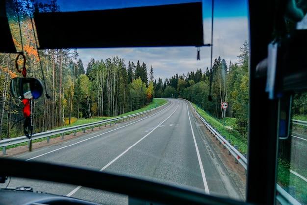 Uitzicht op de weg en het herfstbos door het busraam roadtrip