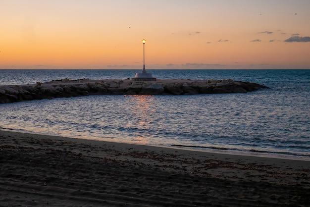 Uitzicht op de zee en de lantaarnpaal op het strand van pedregalejo in de schemering.