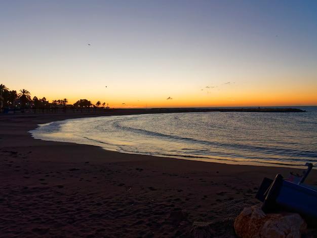 Uitzicht op de zee en de stenen op het strand van pedregalejo in de schemering