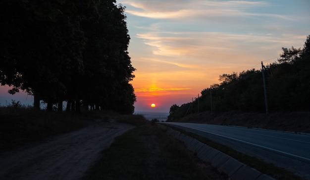 Uitzicht op de zonsondergang op de horizon van asfaltweg.