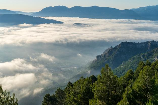 Uitzicht op de zonsopgang vanaf de montcabrer-berg met rechts het cocentaina-kasteel, cocentaina.