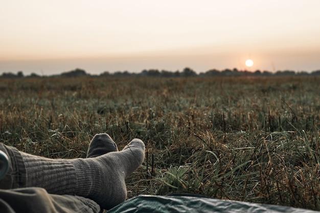Uitzicht op de zonsopgang vanuit de tent, benen, deken en zonsopgang zijn zichtbaar. reis, ontmoet de zonsopgang in de natuur.