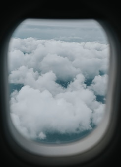 Uitzicht op een bewolkte hemel door het raam van een vliegtuig