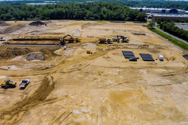 Uitzicht op een grote bouwplaats waar grondverzetapparatuur de grond is om leidingen voor woongebouwen te leggen.