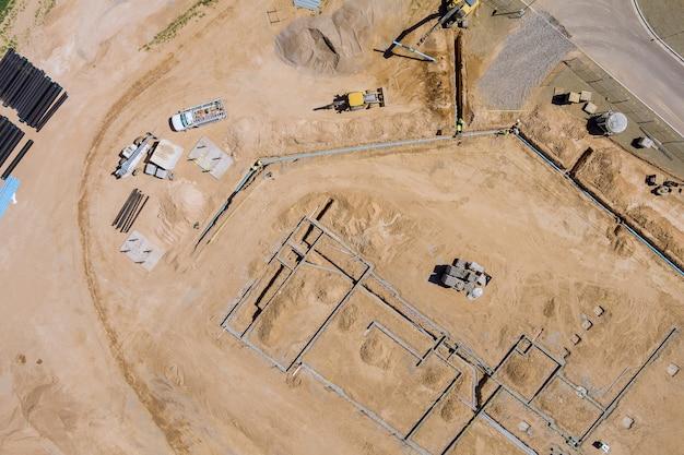 Uitzicht op een grote bouwplaats waar grondverzetmachines de grond leggen om ondergronds te leggen leidingen woongebouwen.