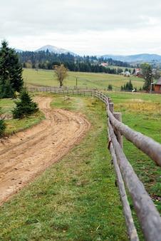 Uitzicht op een houten hek in de karpaten en het pad naar de top.
