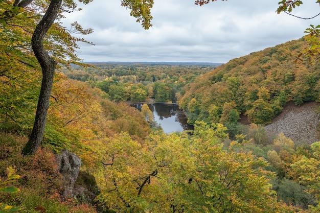 Uitzicht op een kleurrijke herfst bos op zonnige dag weerspiegeld in de kalme wateren van het meer.
