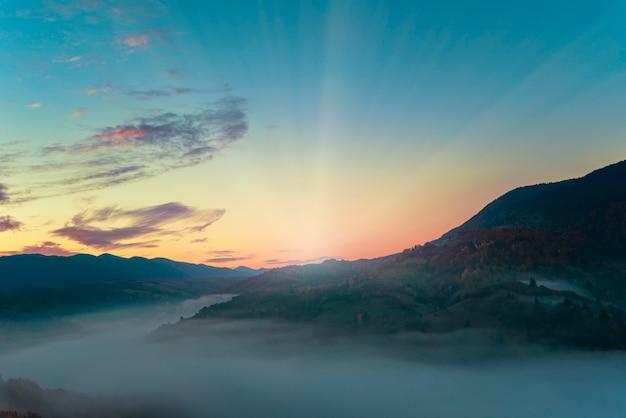 Uitzicht op een prachtig landschap in een heuvelweide met felle rijzende zon op de achtergrond