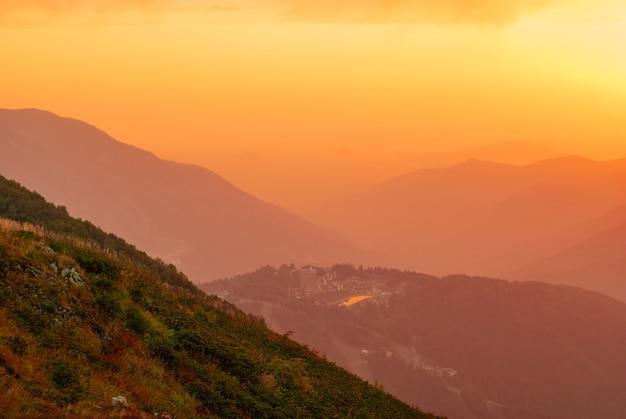 Uitzicht op een prachtige bergvallei met een klein stadje in de zonnestralen