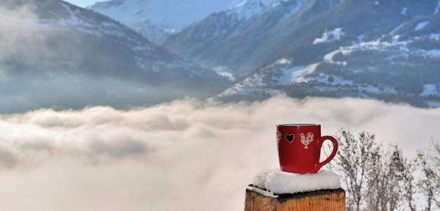 Uitzicht op een rode mok op een besneeuwde paal van een terras boven een zee van wolken in de bergen