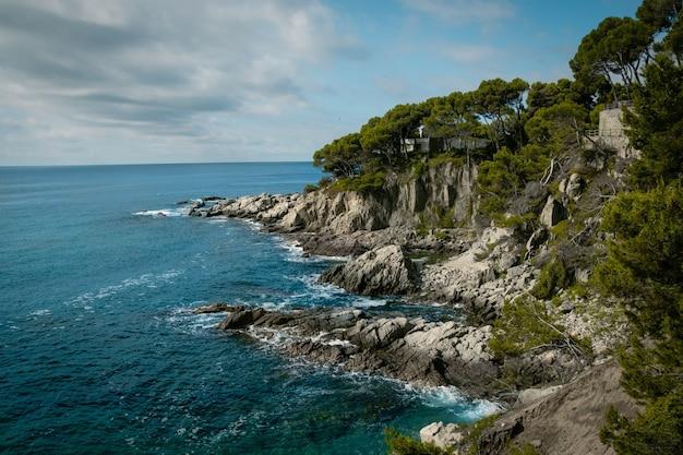 Uitzicht op een rotsachtige kust met een bewolkte blauwe lucht